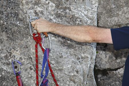 rappelling: A locking carabiner and aknot is on a wall background