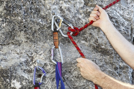 safety harness: Carbine and hook with rope in stone for safety
