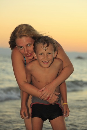 joking: mother and son standing on the beach
