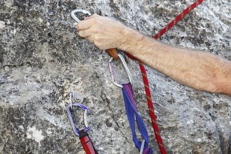 rapell: a hand is clipping a  carabiner for safety climbing