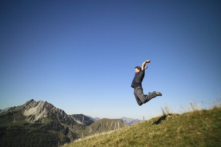 happy  man jumping on meadow against clear sky and mountains background Stock Photo - 10834655