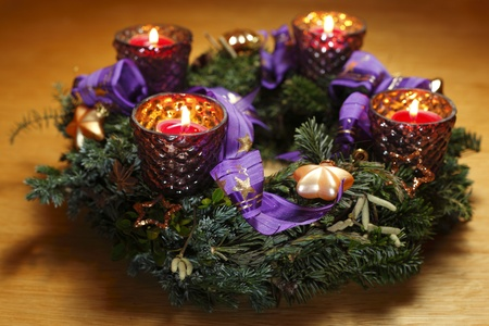 four christmas candles at a round wreath photo
