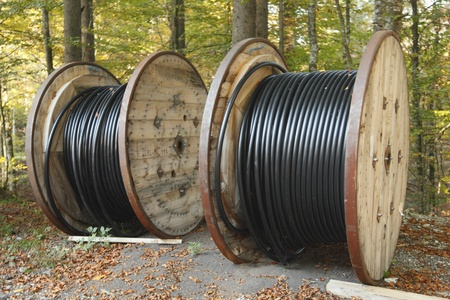 Large rolls of black cables on nature background