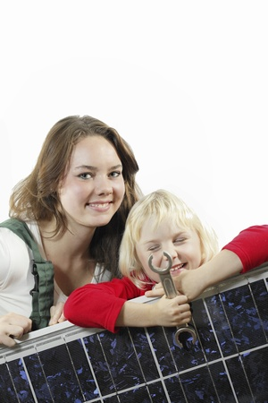 solarenergy: female worker and girl with photovoltaic module and wrench