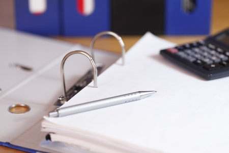 open file folder with pencil and binders in background Standard-Bild