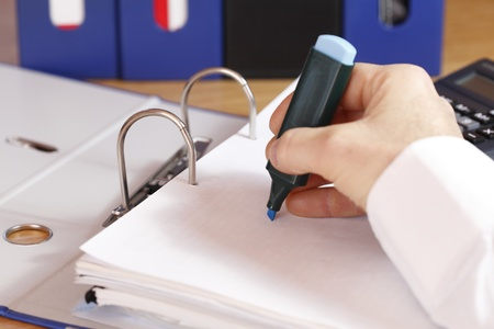 A hand is marking a document at a ring folder photo
