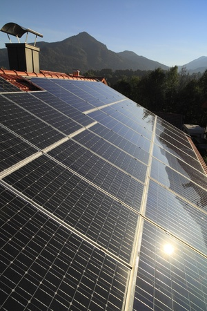Solar panel on roof against landscape with mountains