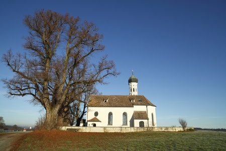 church on a hill at autumn with blue sky photo
