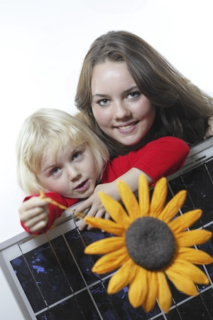 solarpower: two girls with photovoltaic panel and sun symbol Stock Photo