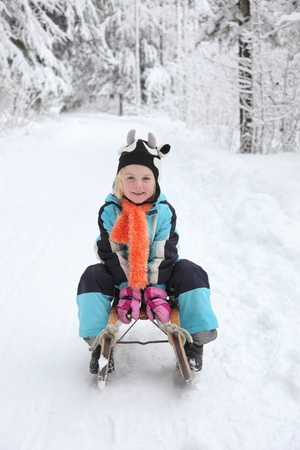 Sledding at winter time.Smiling girl on sleigh. Stock Photo - 11913218