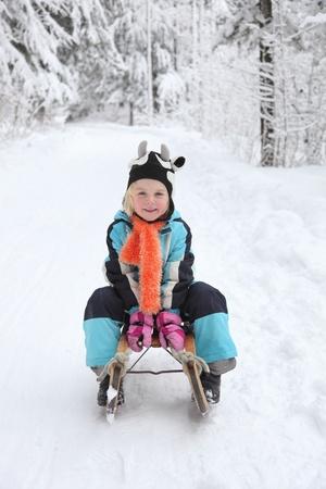 Sledding at winter time.Smiling girl on sleigh. Stock Photo - 11913218
