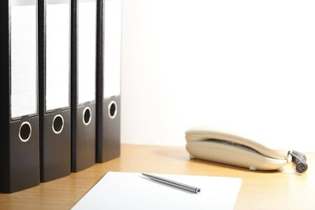 office desk with folders and phone on a white background photo