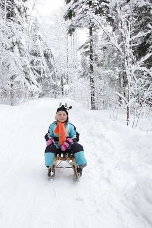 Sledding at winter time.Smiling girl on sleigh. photo