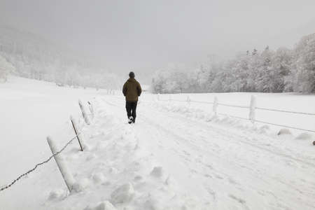 wintery day: a man is hiking in winter way Stock Photo