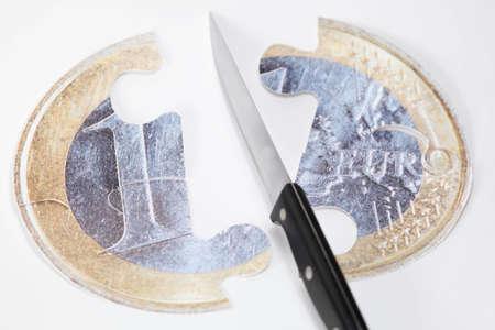 Financial crisis concept: cut and splitting euro coin Stock Photo - 12338428