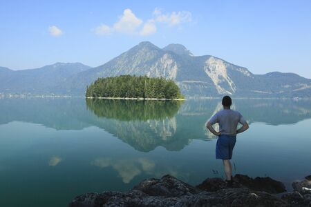 lonesome: man is standing and looking to the lake