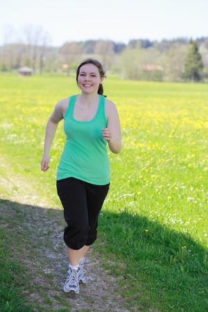 Beautiful young woman runner in nature outdoors
