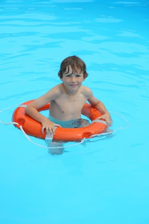 a young boy is swimming in water with safe buoy photo