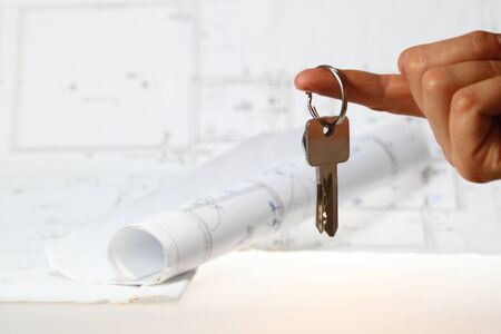 hand is holding key with plan of house in background Stock Photo - 14320400