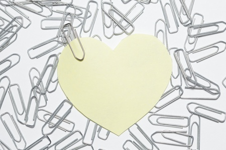 yellow heart sticker with many paper clips Stock Photo - 14616058