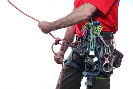 mountaineer with climbing equipment on white background