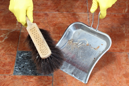 broom and dust pan sweeping up