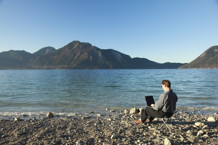 man is working on laptop outdoors,a lake in background