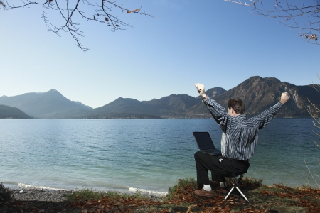 Happy man with raised arms at a laptop, outdoor photo