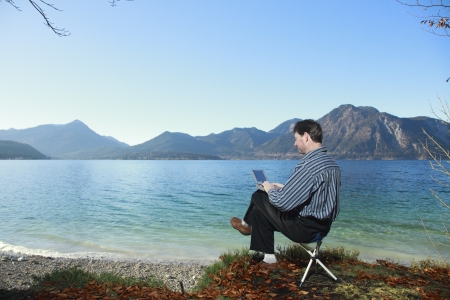 man is working on laptop outdoors,a lake in background photo