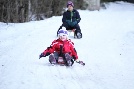girl and woman are sledging in snow photo