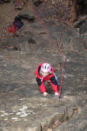 a young girl is climbing a rock wall photo