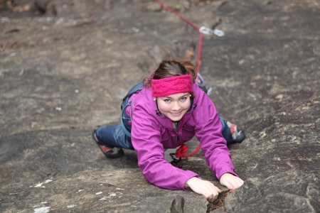 a young woman is climbing a sandstone wall photo