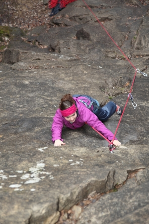 a young woman is climbing on a rock photo