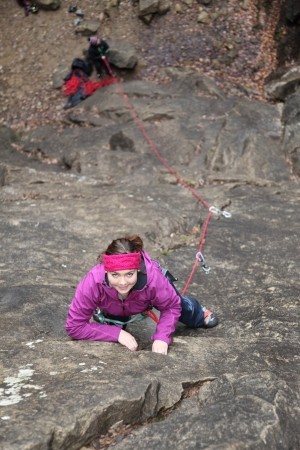 carabineer: a young woman is climbing a  wall