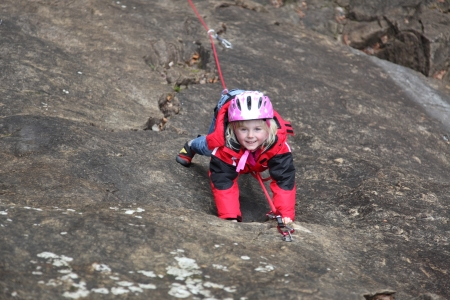 carabineer: a young girl is climbing up a rock