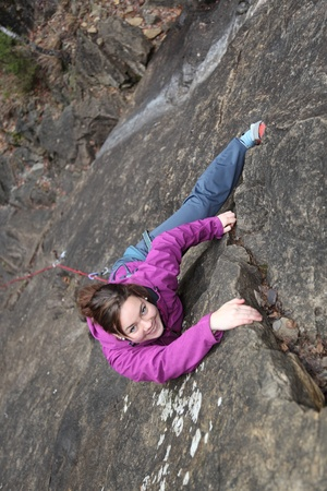 carabineer: a smiling girl is climbing a rock