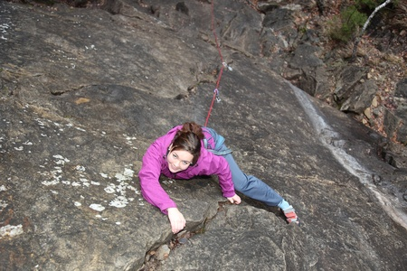 a smiling girl is climbing a rock wall photo