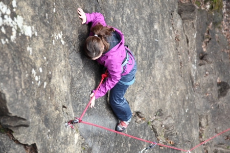 carabineer: a  girl is free climbing a rock