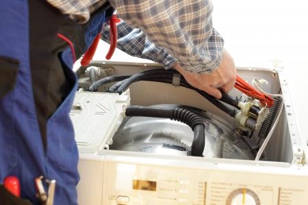 elektricien werkt aan een open wasmachine close up Stockfoto