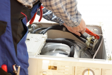 electrician working on a open washing machine close up