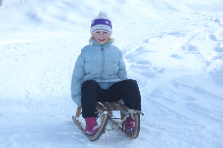 happy girl is sitting on sledge in winter photo