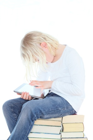 girl with reader is sitting on books photo