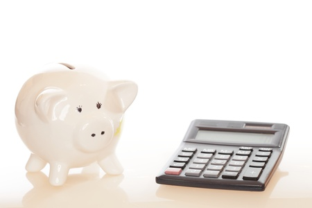 white piggy bank with black calculator on white background photo