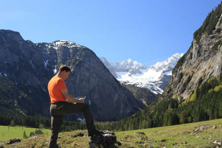 man with mobile technology works in nature photo