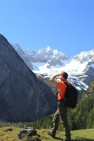 mountain hiking man with white peaks in background photo