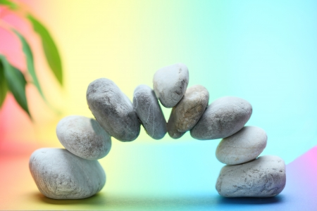 Stack of spa stones  bridge on colored background photo