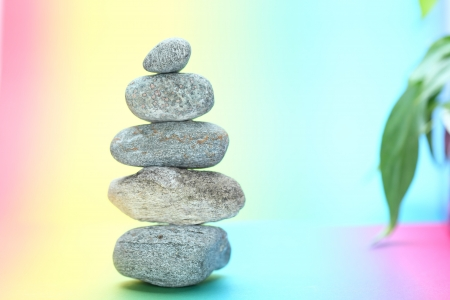 symbolic stone tower in balance with colored background photo