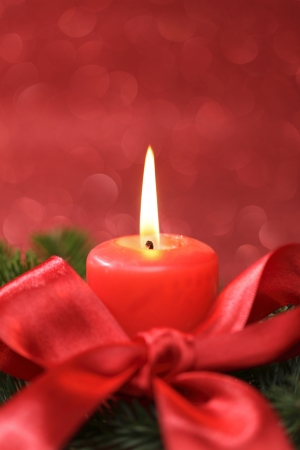 christmas decoration with red candle and red background photo