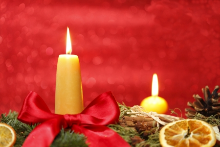 atmospheric: christmas decoration with two yellow candles and red background