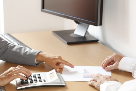 two business people are calculating in office Stock Photo